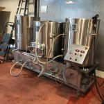 Three-vessel brewhouse fabricated by Portland Kettle Works. Each brew yields 3.5 barrels of wort. Two batches are brewed to fill each 7- barrel fermenter. The brewhouse is a combination RIMS / direct fire system.